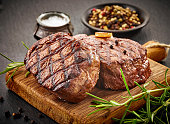 grilled beef steaks with spices on wooden cutting board