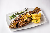Grilled carp fish with rosemary potatoes and lemon on a white plate. View from above. White background