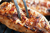 Grilled chicken breast on barbeque, cooking process. Macro shot, shallow depth