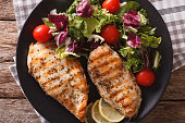Grilled chicken breast with mixed salad on a plate close-up. horizontal view from above