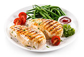 Grilled chicken fillet and vegetables on white background