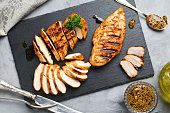 Grilled chicken fillets on slate plate. Gray concrete background