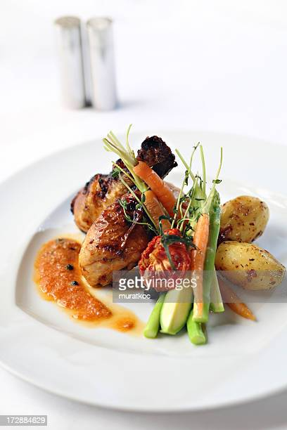 Grilled chicken legs and vegetables on a white plate