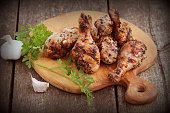 Grilled chicken legs on cutting board.Rustic dinner background.