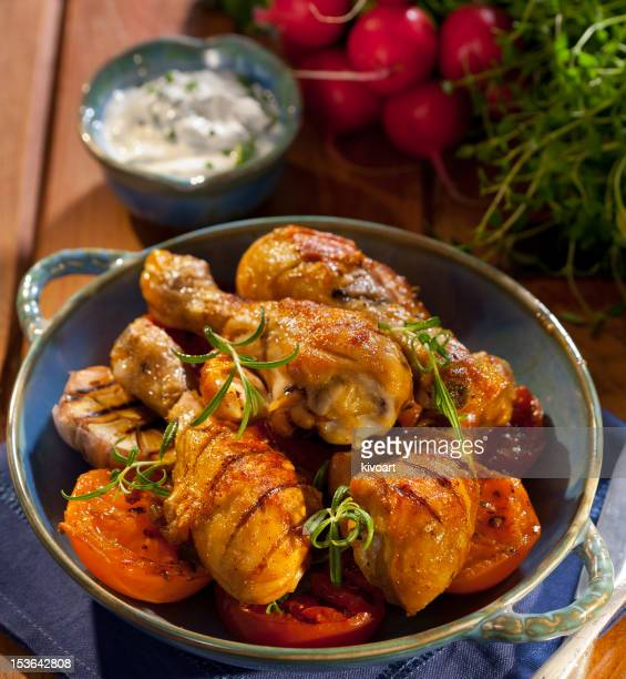 Grilled chicken legs served with tomatoes