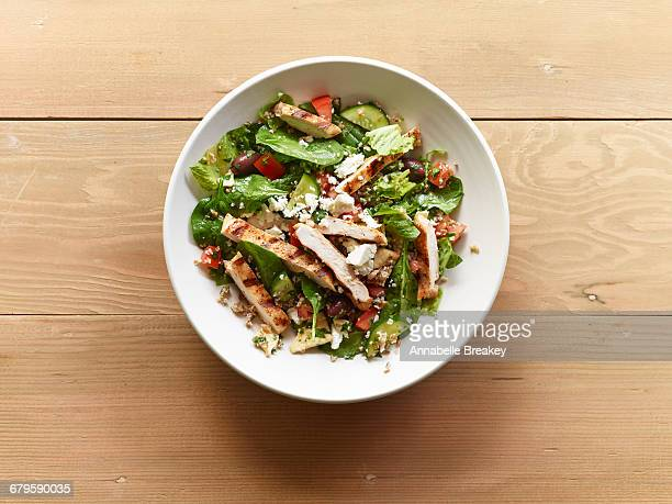 Grilled chicken salad in white bowl on wood