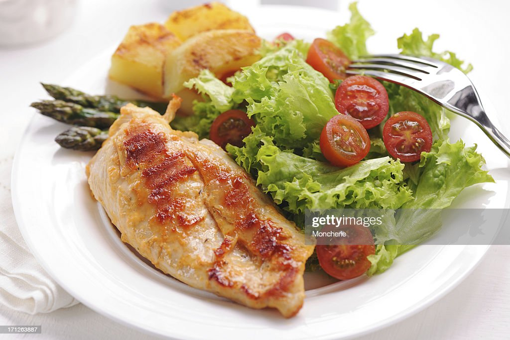 'Grilled chicken steak with potatoes,asparagus and salad'