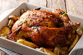 Whole grilled chicken with mushrooms and potatoes close-up in a baking dish. horizontal