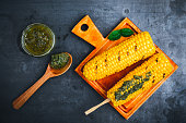 Grilled corn on cob with pesto sauce viewed from above