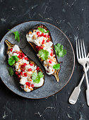 Grilled eggplant with feta, pomegranate, pine nuts and cilantro. Delicious appetizer or snack, on a dark background, top view
