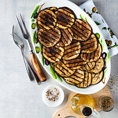 Grilled eggplants seasoned with olive oil on a white stone table