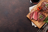 Grilled fillet steak with red wine on stone table. Top view with space for your text