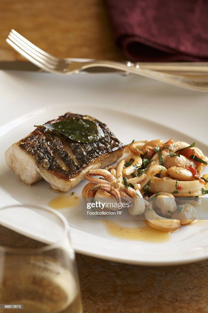Grilled fish with calamari on plate, close-up : Stock Photo