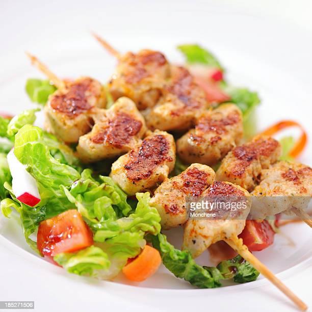 Grilled marinated chicken skewers on raspberry balsamic vinegar salad