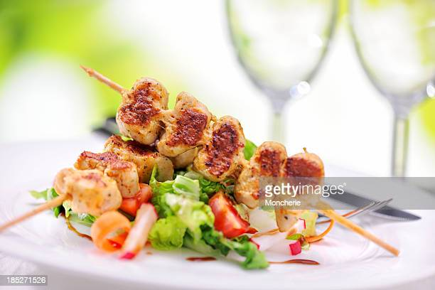 Grilled marinated chicken skewers on raspberry balsamic vinegar salad