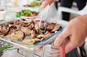 Male hand with tongs catch piece of barbecue meat. Grilled meat and onion on plate close up.
