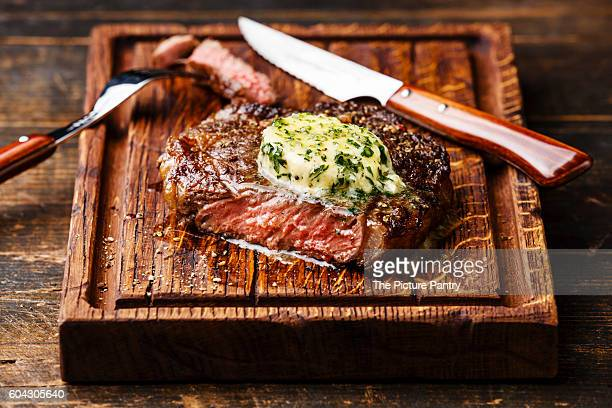 Grilled Medium rare steak Ribeye with herb butter on cutting board