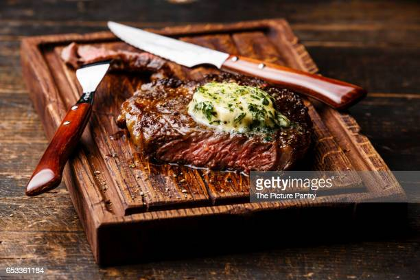 Grilled Medium rare steak Ribeye with herb butter on cutting board serving size