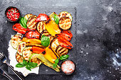 Grilled multicolored vegetables, aubergines, zucchini, pepper with green basil on serving stone board on gray background, top view