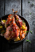 Grilled pheasant with bacon and vegetables on dark background