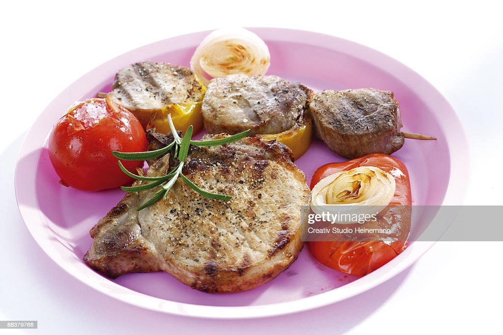 Grilled pork and vegetables in plate, elevated view, close-up : Stock Photo