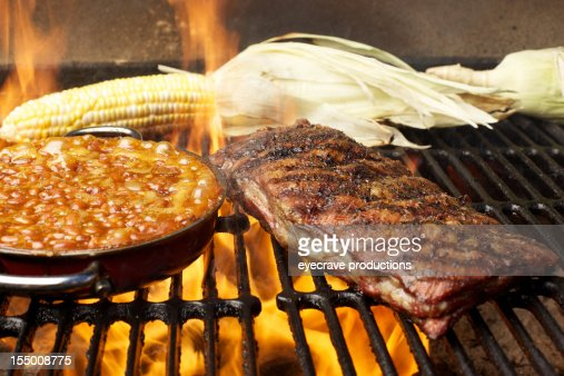 BBQ grilled pork ribs baked beans and corn over flames : Stock Photo