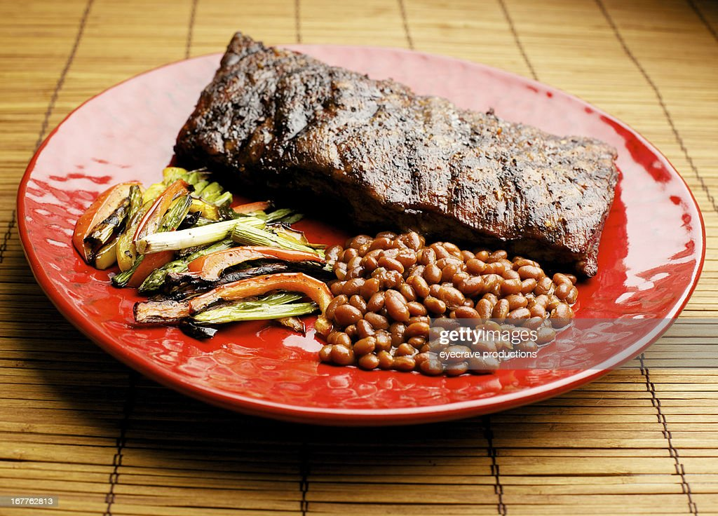 BBQ grilled pork ribs baked beans and vegetables plated : Stock Photo