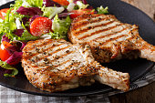 Grilled pork steak with bone and fresh salad close-up on a plate. horizontal