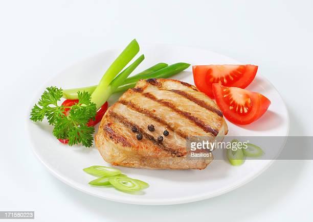 grilled pork steak with vegetable garnish on a plate