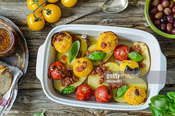 Grilled potatoes with tomato pesto, tomatoes and basil leaves