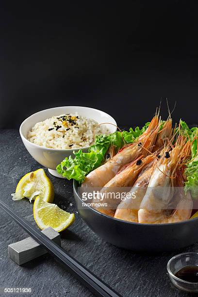 Grilled prawn and vegetables in bowl on moody background.