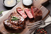 Grilled ribeye beef steak, herbs and spices on cutting board