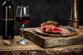 Grilled ribeye beef steak with red wine, herbs and spices on wooden table. Still life