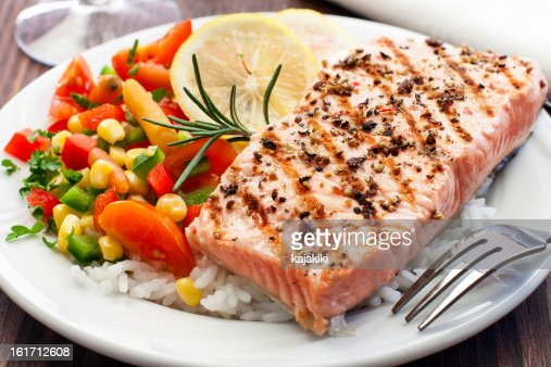 A grilled salmon followed by fresh rice and vegetables