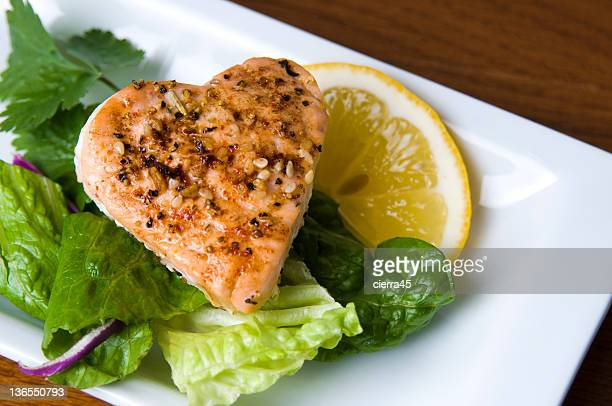 Grilled salmon in a heart shape on salad with slice of lemon