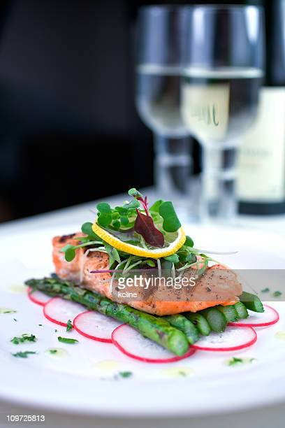 Grilled salmon on a bed of asparagus served on a white plate