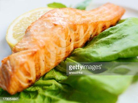Grilled Salmon on green salad leaf with lemon
