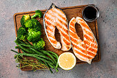 Cutting board with grilled salmon steaks and vegetables on gray table, top view