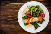 Grilled salmon with asparagus and arugula on wooden table
