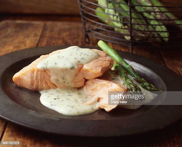 Grilled salmon with asparagus and sauce on pewter plate