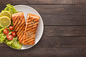 Grilled salmon with lemon, tomato on the wooden background. Copyspace for your text.
