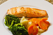 Grilled salmon dish with steamed vegetables.