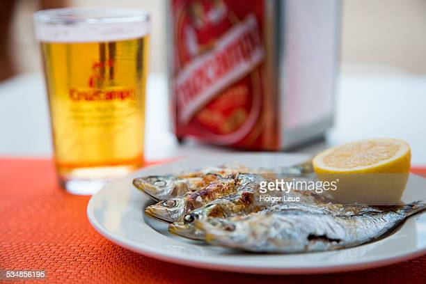 Grilled sardines and beer at beach restaurant