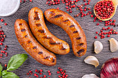 Grilled sausage with spices on a dark wooden background.