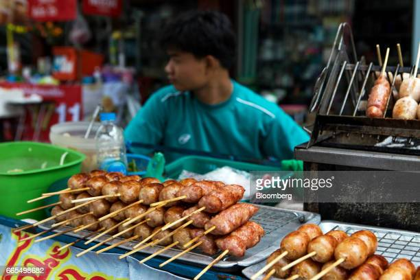Grilled sausages and other meat snacks sit on display at a food stall in the Phaya Thai District of Bangkok Thailand on Wednesday April 5 2017 The...