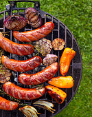Grilled sausages and vegetables on a grilled plate, outdoor, top view. Grilled food, bbq
