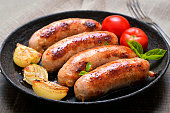 Grilled sausages and vegetables in frying pan, close up