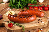 Grilled sausages with vegetables and spices on wooden background