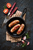 Grilled pork sausages or bangers in cast iron skillet or frying pan with tomatoes, garlic and rosemary. Overhead view