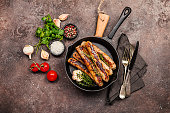 Grilled sausages with tomato sauce in a pan on brown stone background, top view